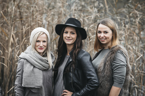 Portrait of three smiling friends in autumnal nature - HMEF00117