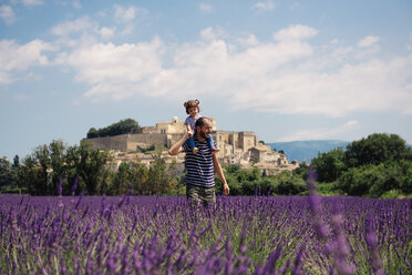 France, Grignan, father carrying little daughter on his shoulders through lavender field - GEMF02602