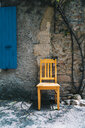 France, Grignan, yellow wooden chair in front of an old house - GEMF02605