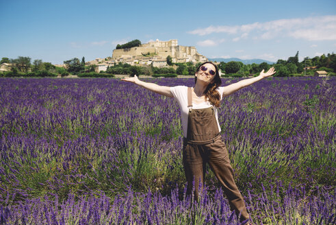 France, Grignan, happy woman standing in lavender field - GEMF02617