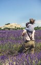 France, Grignan, back view of mother standing in lavender field with little daughter on her shoulders - GEMF02626