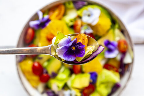 Spoon of mixed salad with avocado, tomatoes and edible flower, close-up - SARF03984