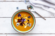 Bowl of creamed pumpkin soup garnished with edible flowers - SARF03987
