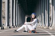 Portrait of woman sitting over skateboard on road under bridge - CAVF56762