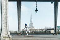 Side view of woman skateboarding under bridge against Eiffel Tower - CAVF56765
