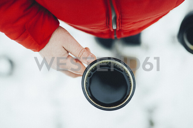 Midsection of woman holding mug with black coffee during winter - CAVF56792