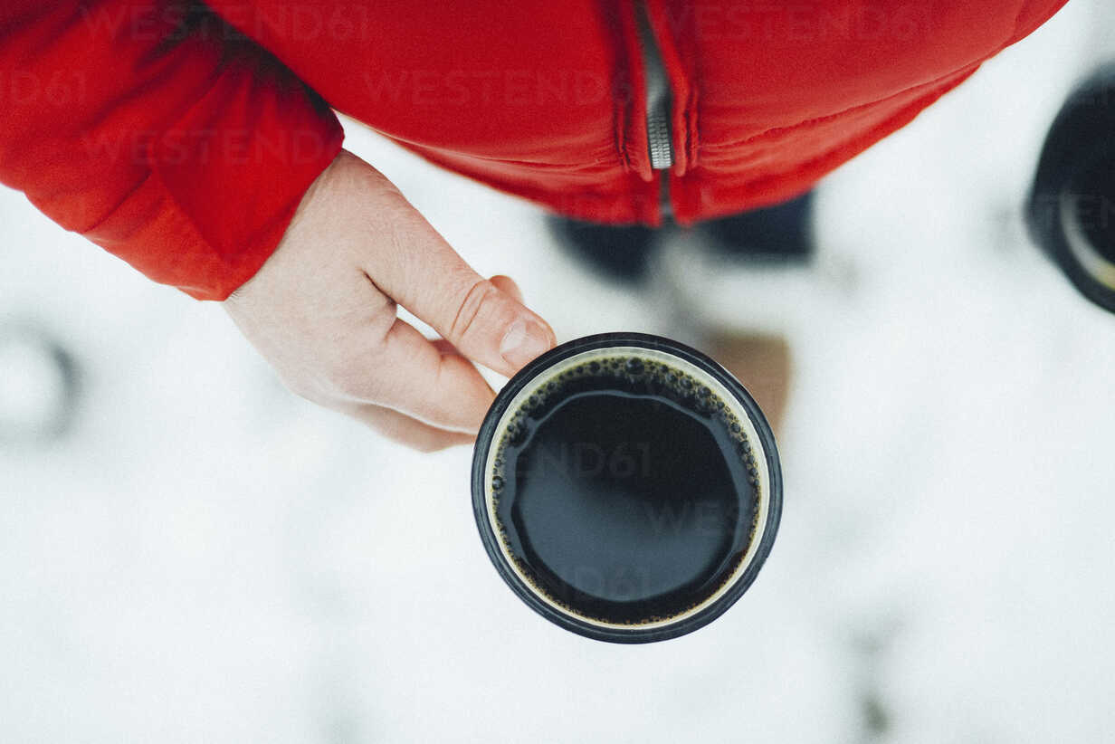 Midsection of woman holding mug with black coffee during winter - CAVF56792 - Cavan Images/Westend61