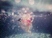 Low section of girl in swimwear swimming in pool - CAVF56807