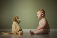 Shirtless baby boy looking at stuffed toy while sitting on floor against wall at home - CAVF56822