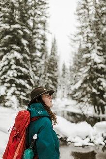 Side view of woman with backpack standing in snow covered forest - CAVF56858