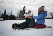 Side view of siblings on sled against cloudy sky - CAVF56876