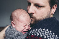 Close-up of father kissing crying son at home - CAVF56885