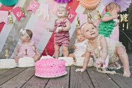 Cute baby girls with birthday cakes on floorboard at party - CAVF56900