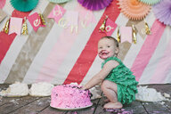 Cheerful baby girl looking away while eating birthday cake on floorboard during party - CAVF56906