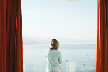 Woman looking at sea while standing in balcony against sky - CAVF56927