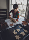 Boy rolling cookie dough on table during Christmas at home - CAVF56939