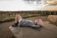 Carefree girl with hands behind head lying on rock in city - CAVF56987