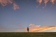 Rear view of girl standing on field against sky during sunset - CAVF56990