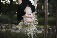Portrait of playful girl hanging on monkey bars at playground - CAVF57032