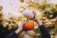 Cropped image of girl balancing pumpkins on head at field - CAVF57038