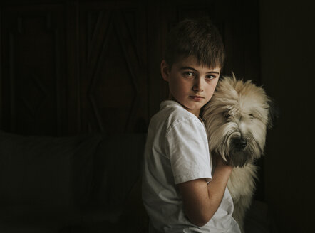 Portrait of boy with dog standing in darkroom at home - CAVF57071