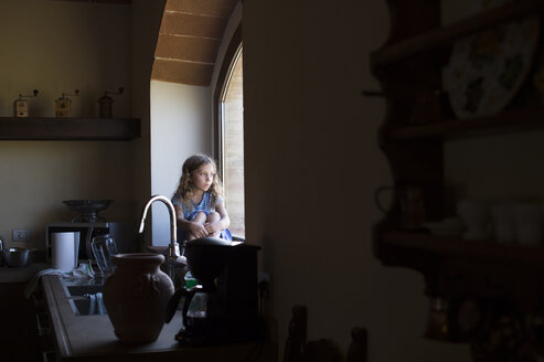 Girl looking through window while sitting in kitchen at home - CAVF57077
