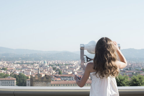 Rear view of girl looking through coin-operated binoculars by cityscape against clear sky - CAVF57080