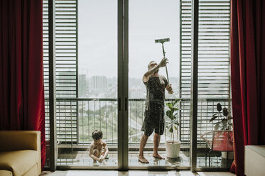 Father with son cleaning windows in balcony seen through glass - CAVF57161