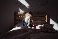 Girl embracing doll while sitting on bed in darkroom at home - CAVF57182