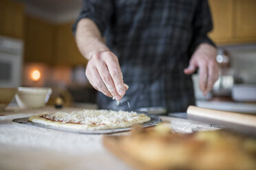 Midsection of man sprinkling ingredients on pizza at kitchen - CAVF57227