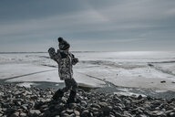 Boy standing on stones by frozen sea against sky - CAVF57239