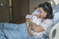Mother kissing newborn son while relaxing on bed at hospital - CAVF57275