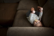 High angle portrait of baby boy drinking milk from bottle while lying on sofa at home - CAVF57287
