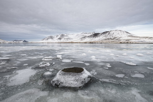 Scenic view of frozen lake against snowcapped mountains and cloudy sky - CAVF57305