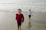 Portrait of cheerful boy with brother standing in background on shore - CAVF57323
