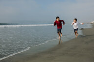 Full length of playful brothers running on shore at beach - CAVF57326