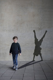 Germany, Duesseldorf, portrait of laughing little boy and shadow of Duesseldorf's cartwheeler on wall - PSTF00262