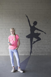 Portrait of smiling blond girl with smartphone and shadow of ballerina in the background - PSTF00265