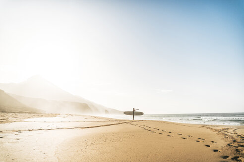 Man with surfboard standing on shore at beach against sky during foggy weather - CAVF57366