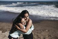 Cheerful friends embracing at beach - CAVF57393