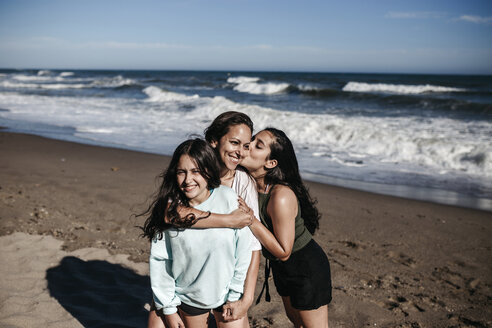 Mother with daughters standing at beach against sky during sunny day - CAVF57396