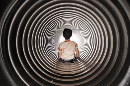 Rear view of boy sitting in huge metallic pipe - CAVF57420