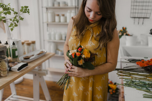 Florist looking at bouquet while standing at flower shop - CAVF57435