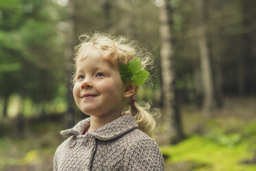 Playful girl with leaves on ear at forest - CAVF57447