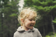 Cheerful girl with blond hair at forest - CAVF57450
