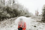Boy with umbrella standing in forest during winter - CAVF57459
