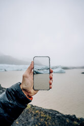 3D montage of man taking smartphone picture of Iceland's landscape - OCMF00124