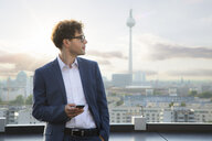 Germany, Berlin, businessman with smartphone on roof terrace in the evening - FKF03118