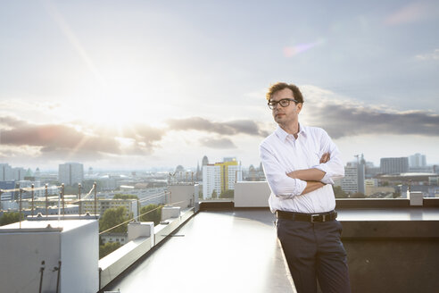 Germany, Berlin, businessman standing on roof terrace looking at distance in the evening - FKF03124