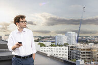 Germany, Berlin, businessman with cell phone standing on roof terrace looking at view - FKF03127